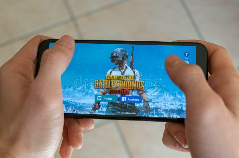 Italia, Roma - 7 de marzo de 2019: Manos que sostienen un smartphone con el juego móvil de los campos de batalla de PUBG en la pa foto de archivo