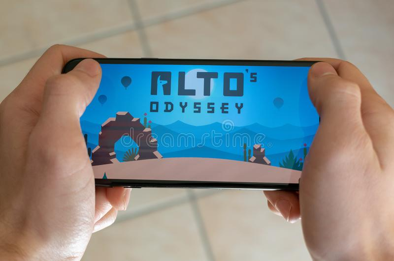 Italia, Roma - 7 de marzo de 2019: Manos que sostienen un smartphone con el juego de Odyssey Mobile del alto en la pantalla de vi imagen de archivo libre de regalías