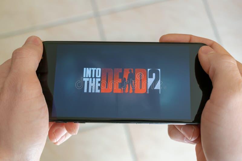 Italia, Roma - 7 de marzo de 2019: Manos que sostienen un smartphone con en el juego muerto de 2 móviles en la pantalla de visual foto de archivo libre de regalías