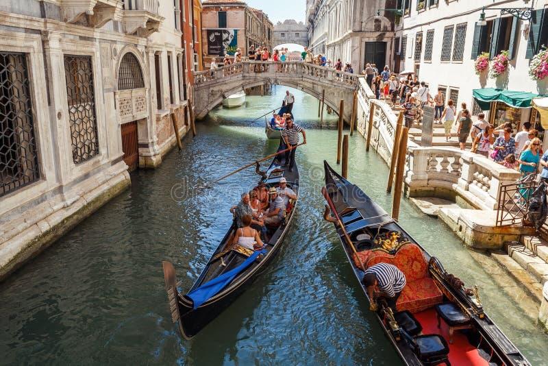 ITALIA, VENECIA - JULIO DE 2012: Góndolas con los turistas que cruzan un pequeño canal veneciano el 16 de julio de 2012 en Venecia fotografía de archivo