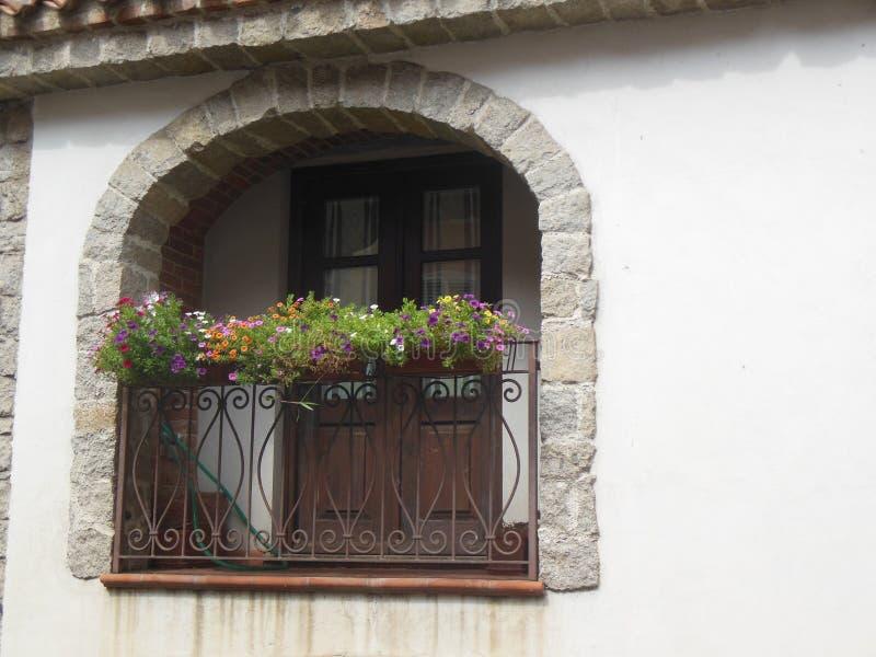 Italiaans balkon met bloeiende installaties stock afbeeldingen