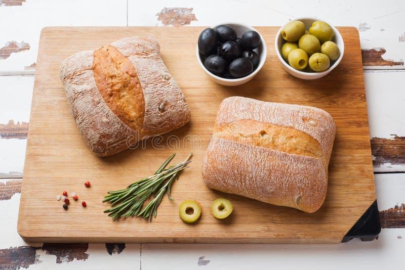 Italiaans ciabattabrood met olijven en rozemarijn op een houten Raad royalty-vrije stock afbeeldingen