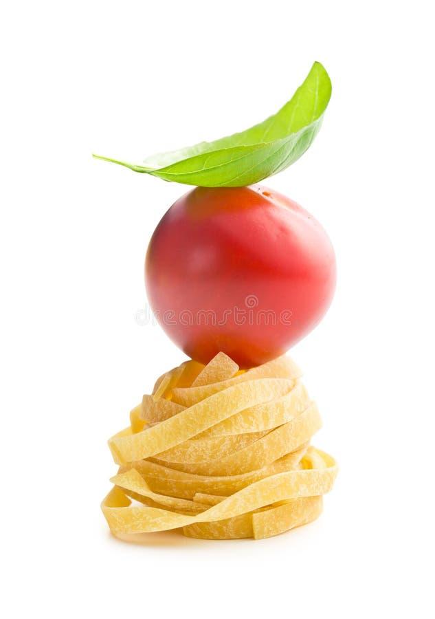 Italiaans deegwarentagliatelle, tomaat en basilicumblad stock foto's