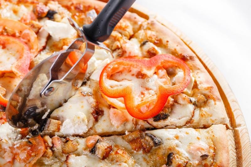 Italiaans keuken en het koken concept - kook met snijder scherpe pizza aan stukken bij pizzeria Hete smakelijk gesneden met zalm royalty-vrije stock foto