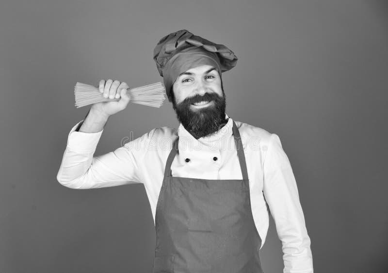 Italiaans restaurantconcept De kok met vrolijk gezicht houdt droge deegwaren royalty-vrije stock foto