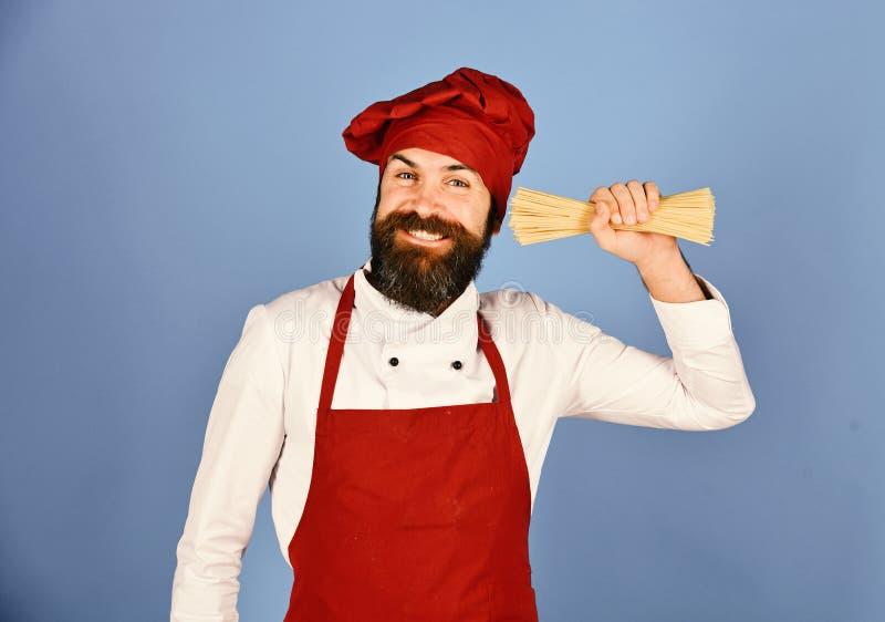 Italiaans restaurantconcept De kok met vrolijk gezicht houdt droge deegwaren royalty-vrije stock foto's