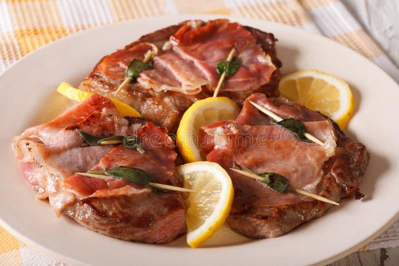 Italiaans rundvlees Saltimbocca met salie, ham en citroenclose-up Hori royalty-vrije stock afbeeldingen