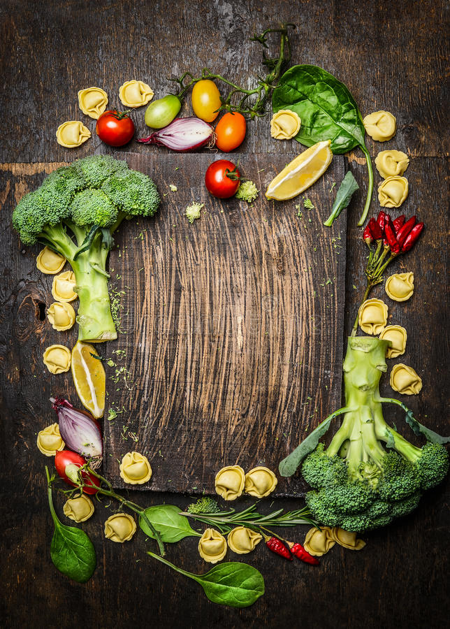 Italiaans voedselconcept met tortellinideegwaren en verse organische groenten op donkere rustieke houten achtergrond stock afbeelding