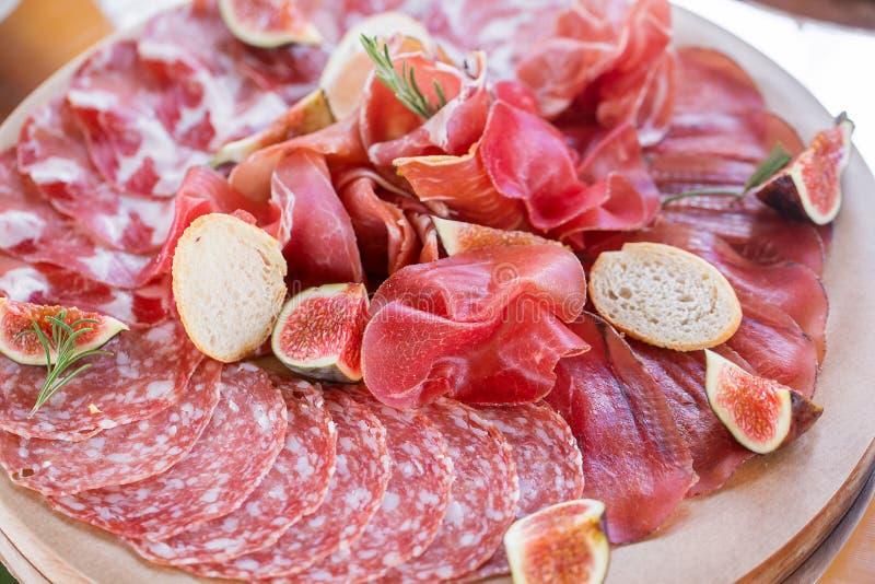 Italiaanse antipasti en voorgerechten raad met plakkenprosciutto, salami, droog varkensvlees, salamiham met kruiden stock foto