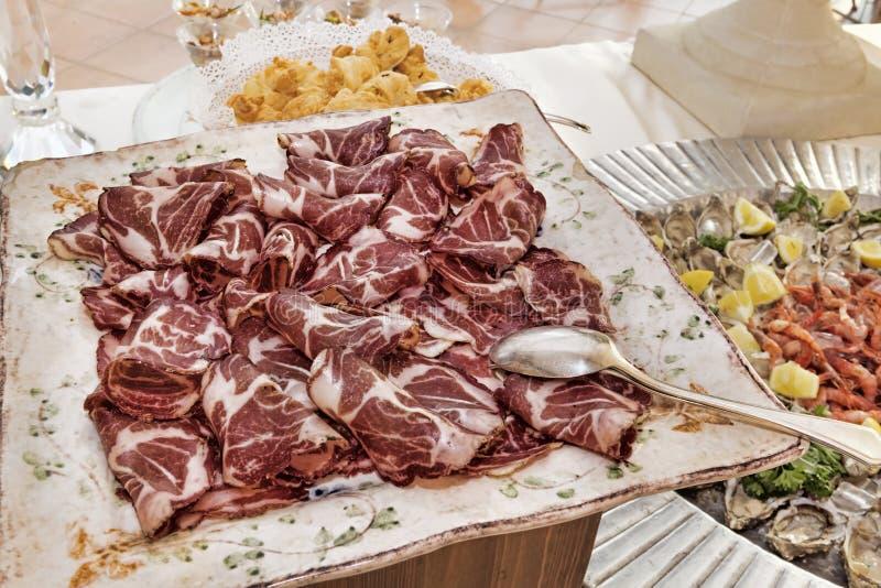 Italiaanse aroma's: gesneden bacon in een dienende die schotel op een elegante lijst wordt geplaatst stock foto