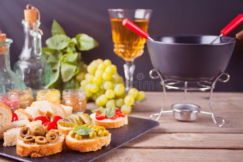 Italiaanse bruschetta in assortiment op de plaat, glazen met witte wijn, druiven, fondue Partij of dinerconcept stock foto's