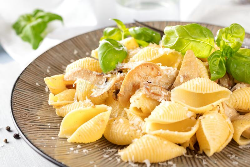 Italiaanse deegwaren in een romige saus met salade op een plaat, close-up stock afbeeldingen