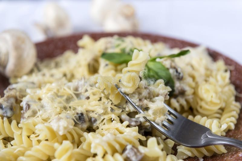 Italiaanse deegwaren met paddestoelen, kaas en Basilicum stock foto's
