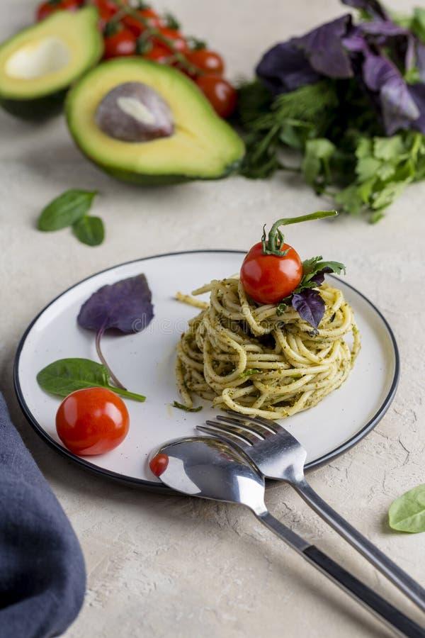 Italiaanse deegwaren met pesto, kruiden en kersentomaten bij witte plaat royalty-vrije stock foto's