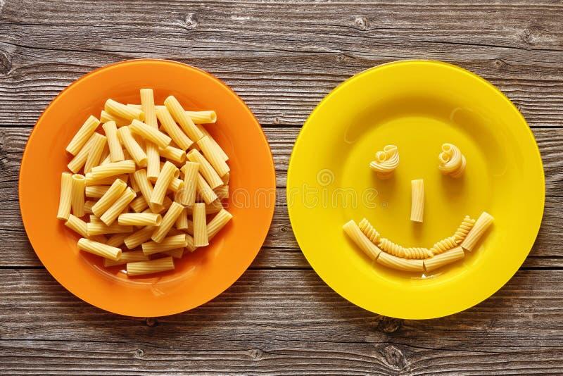 Italiaanse deegwaren in oranje plaat en glimlach met deegwaren op een houten achtergrond royalty-vrije stock foto's
