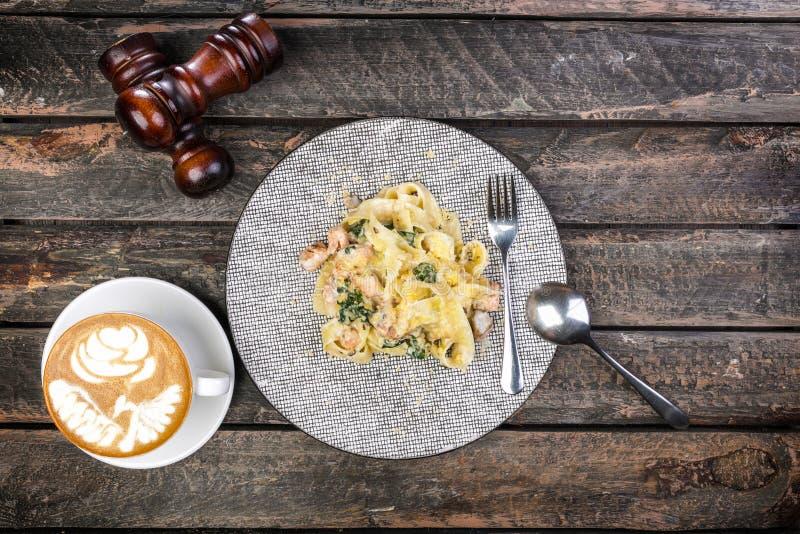 Italiaanse deegwarenfettuccine in een romige die saus met garnalen op een plaat, met het de verfraaide bestek en kop van koffie w stock foto