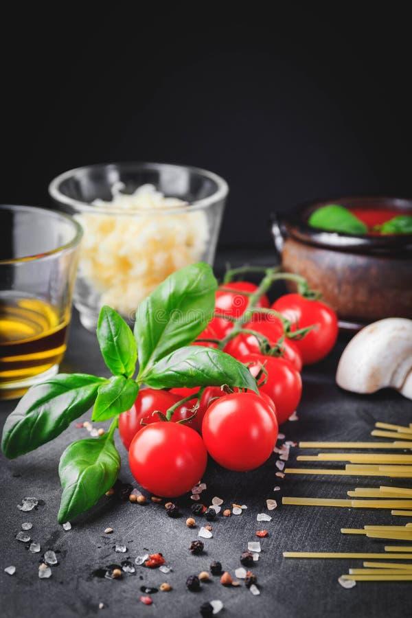 Italiaanse deegwareningrediënten Kers-tomaten, spaghettideegwaren, knoflook, paddestoel, basilicum, olijfolie, mozarella en kruid royalty-vrije stock fotografie