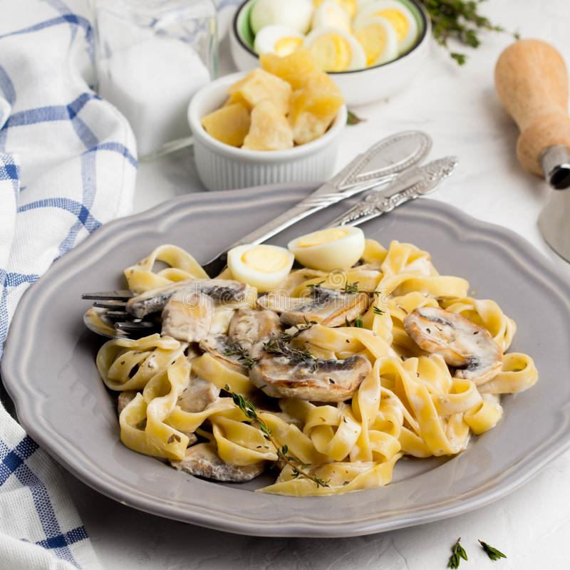 Italiaanse deegwarentagliatelle met de saus van de paddestoelroom, kaas stock foto