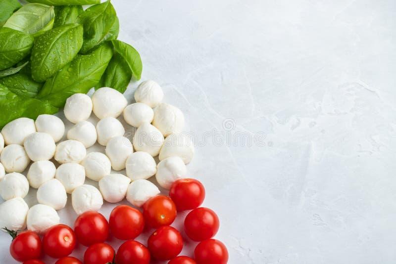 Italiaanse die vlag met Tomatenmozarella en Basilicum wordt gemaakt Het concept Italiaanse keuken op een lichte achtergrond Hoogs stock foto