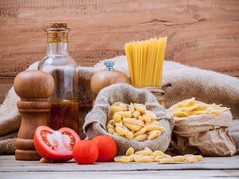 Italiaanse diverse deegwaren van het voedselconcept met op smaak gebrachte olijfolie en s stock foto