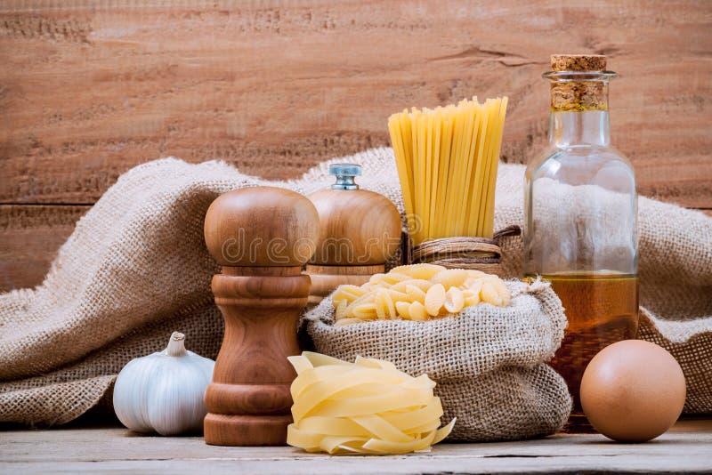 Italiaanse diverse deegwaren van het voedselconcept met op smaak gebrachte olijfolie en s stock foto's