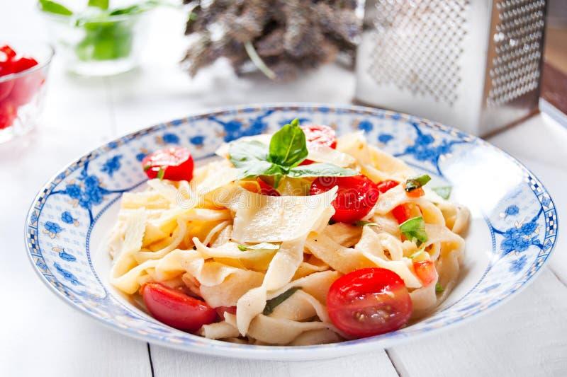 Italiaanse fettuccinedeegwaren met kersentomaten en parmezaanse kaas royalty-vrije stock foto
