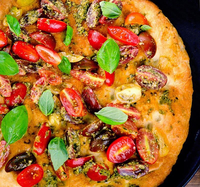 Italiaanse focaccia met tomaten, basilicum en pesto stock foto