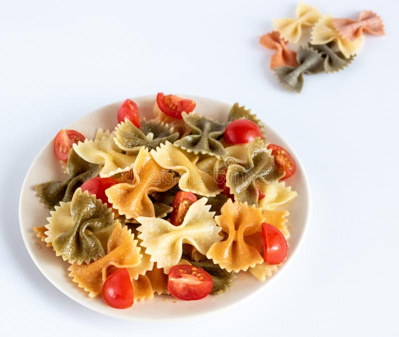 Italiaanse gekleurde deegwaren farfalle met basilicum en tomaten op de witte achtergrond royalty-vrije stock foto's