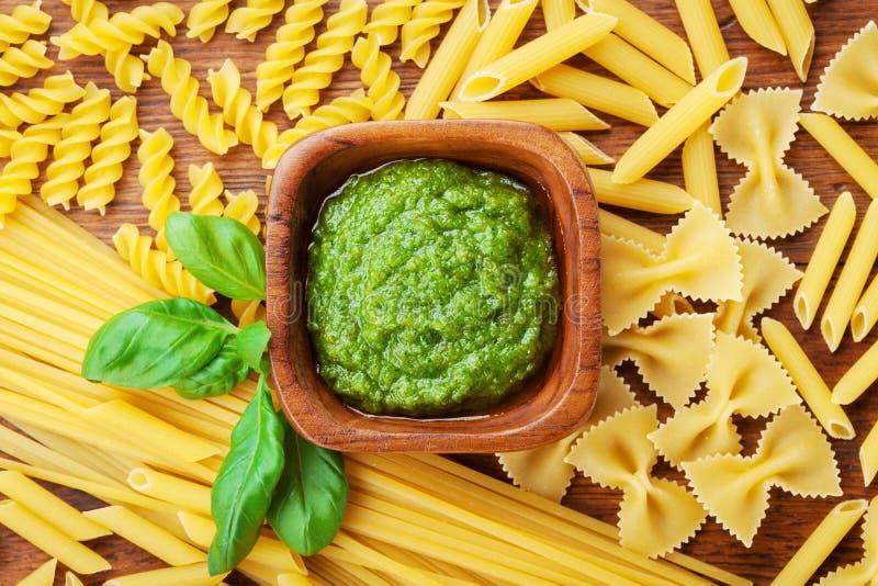Italiaanse groene pestosaus en gemengde ruwe deegwaren hoogste mening Het concept van het voedsel royalty-vrije stock fotografie