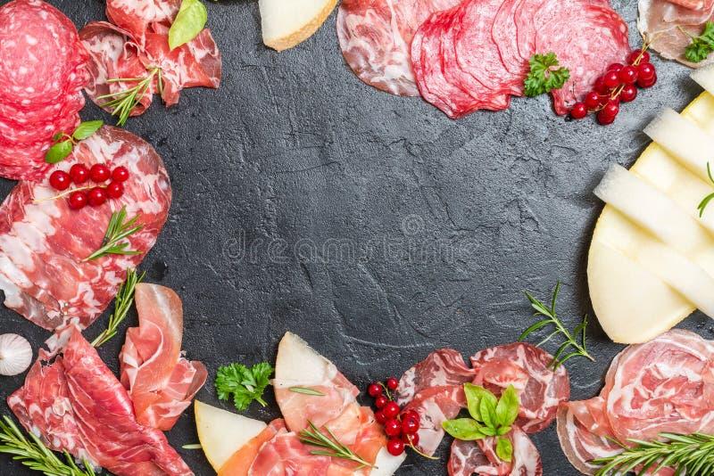 Italiaanse ham, prosciutto en salami met meloen stock afbeelding