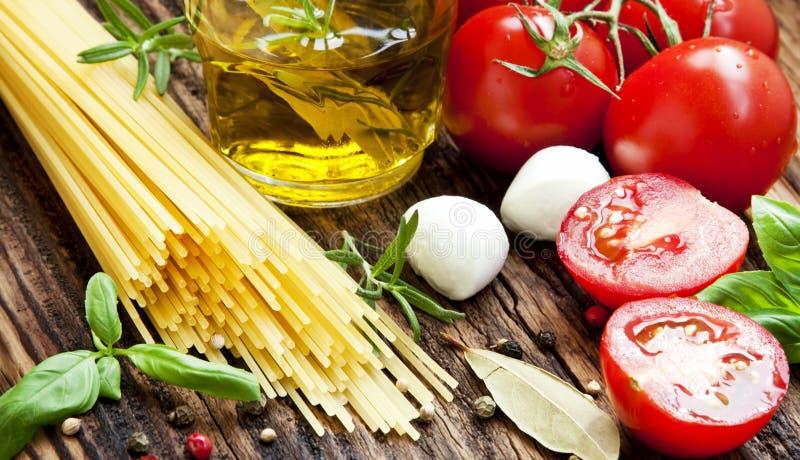 Italiaanse Ingrediënten, Spaghetti, Olive Oil, Kruiden, Cherry Tomatoe royalty-vrije stock foto's