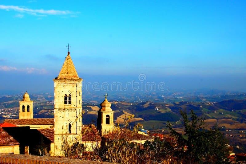 Italiaanse katholieke kerk met mooi heuvelig landschap op de achtergrond stock fotografie