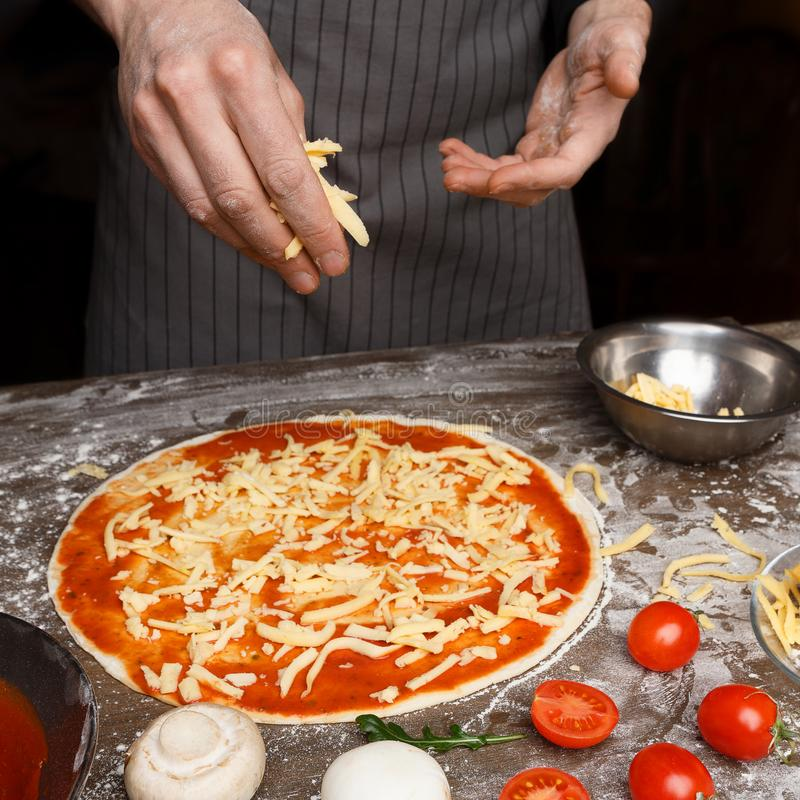 Italiaanse keuken De Kaas van kokhand adding grated aan Pizza royalty-vrije stock afbeeldingen