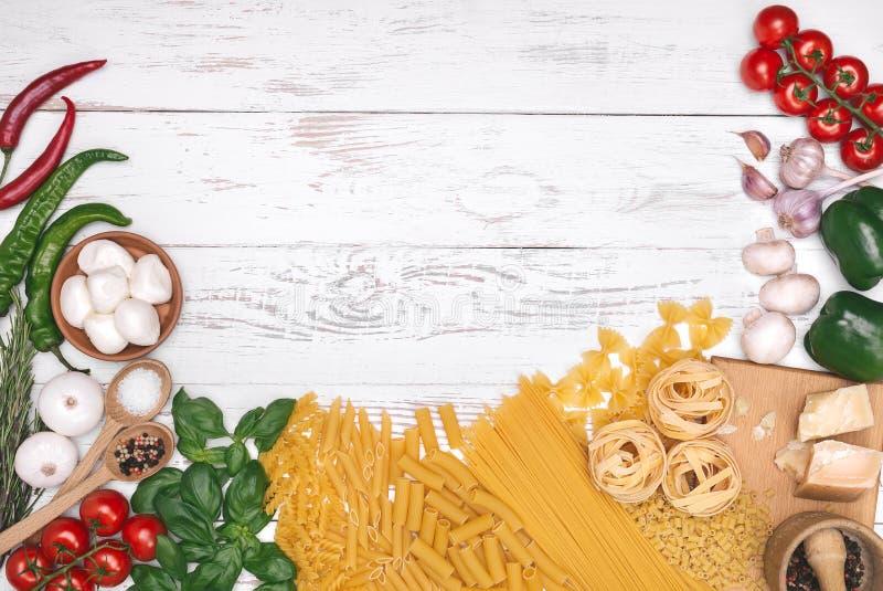 Italiaanse keuken Groenten, olie, kruiden en deegwaren op witte houten lijstachtergrond, hoogste mening royalty-vrije stock afbeelding