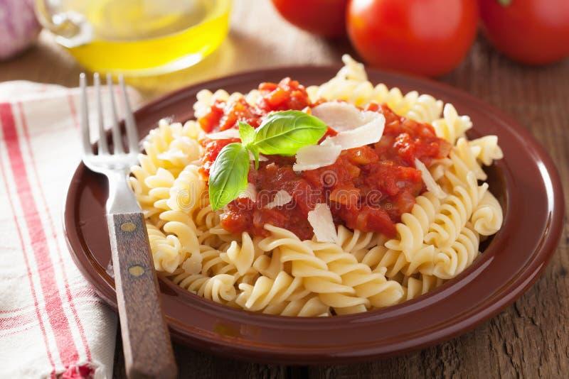 Italiaanse klassieke deegwarenfusilli met tomatensaus en basilicum stock afbeeldingen