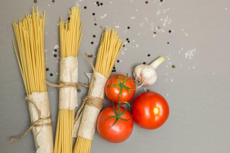 Italiaanse macaroniingrediënten op een grijze achtergrond, hoogste mening, exemplaarruimte stock afbeelding