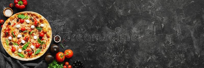 Italiaanse pizza en pizza kokende ingrediënten op zwarte concrete achtergrond royalty-vrije stock foto's