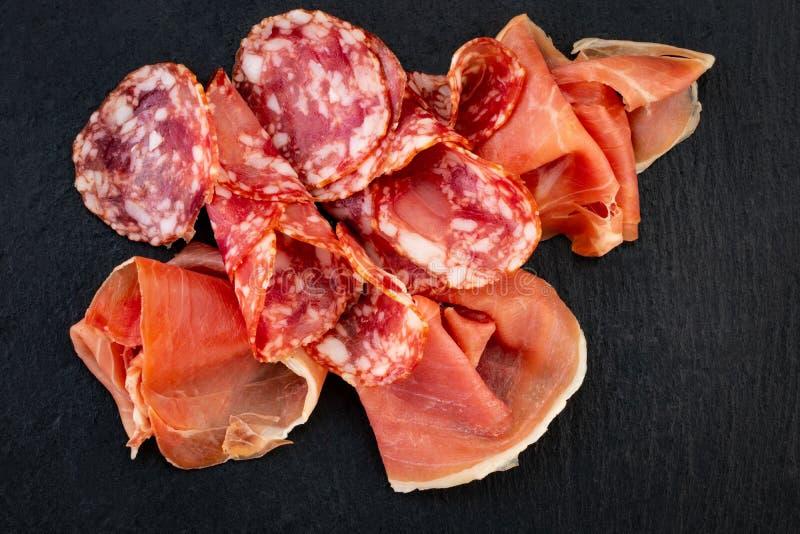 Italiaanse prosciuttocrudo of Spaanse jamon en worsten Ruwe ham op steen scherpe raad stock afbeelding