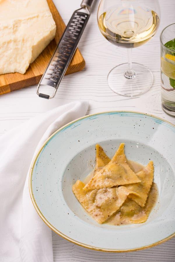Italiaanse raviolideegwaren op plaat met stuk van Parmezaanse kaas en witte wijn royalty-vrije stock afbeelding
