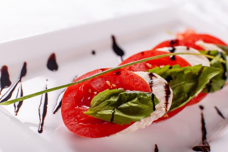 Italiaanse Salade Caprese Mozarellakaas, tomaten en de bladeren van het basilicumkruid Balsemieke die azijn op witte plaat wordt  stock fotografie