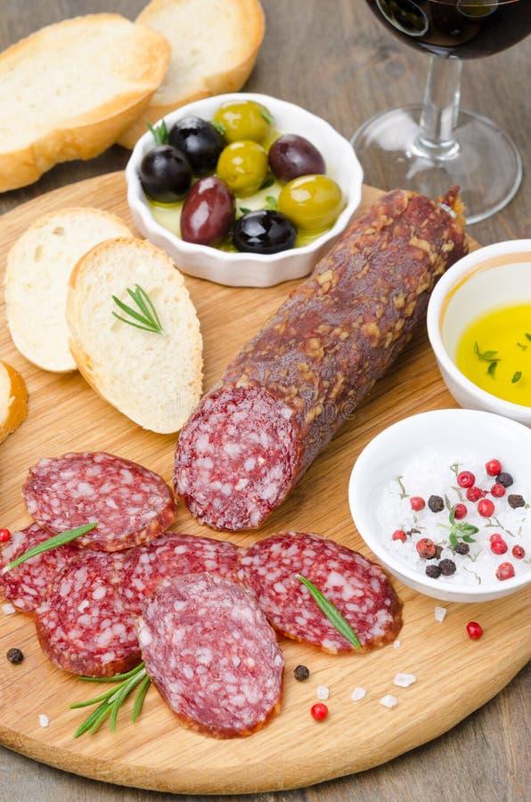 Italiaanse salami, brood, olijven en kruiden op een scherpe raad royalty-vrije stock foto's