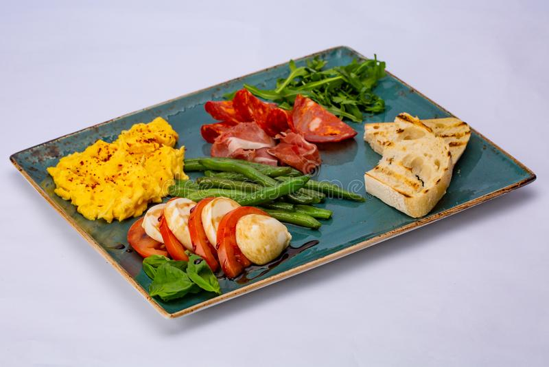 Italiaanse snackomelet met aspagagus, tomaat, arugula, salami, prosciutto en toost royalty-vrije stock fotografie