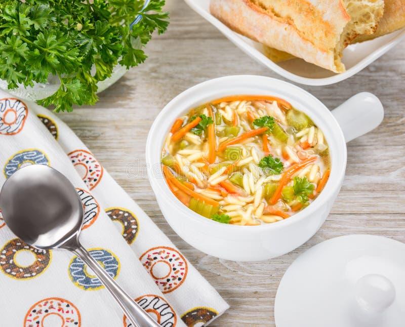 Italiaanse soep met orzodeegwaren De soep van kippenorzo in een witte slijpstof op houten achtergrond royalty-vrije stock afbeelding