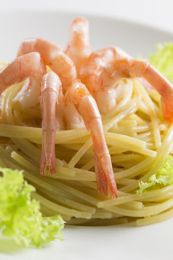 Italiaanse spaghetti met langounginamigarnalen en groene salade Zeevruchtendeegwaren met olijfolie, staarten de zonder hoofd van  royalty-vrije stock afbeeldingen