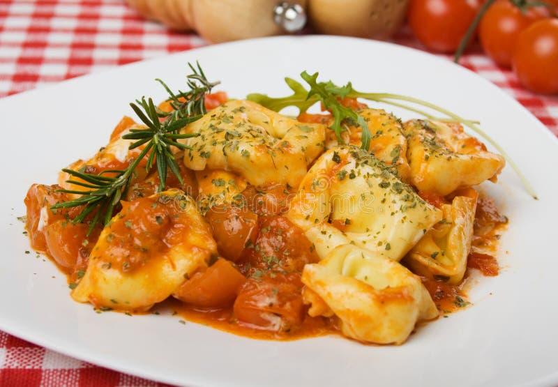Italiaanse tortellinideegwaren met tomatensaus stock foto's