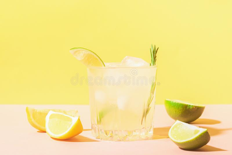 Italiaanse traditionele dranklimoncello in glasdrinkbekers op pastelkleur gele roze achtergrond Alcoholische cocktail De ruimte v stock foto's