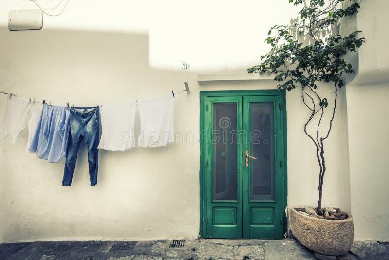 Italiaanse uitstekende scène Kleren die aan droog en oud huis hangen stock afbeelding