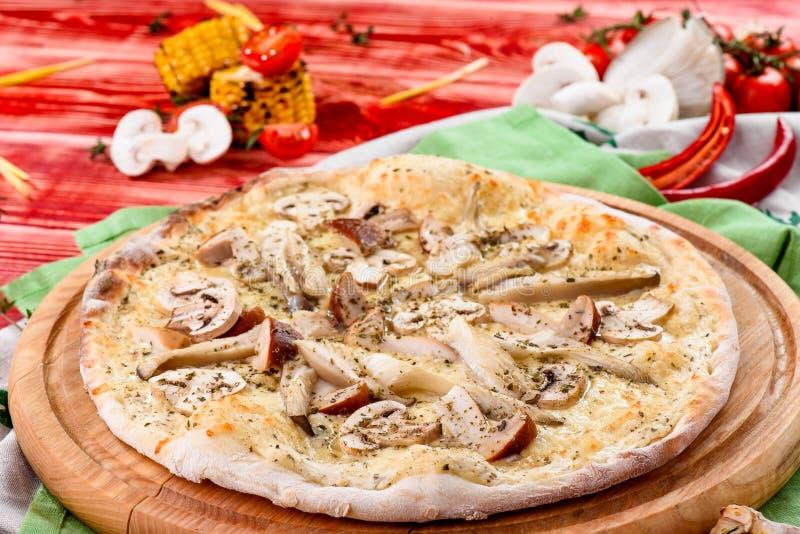 Italiaanse Vegetarische Paddestoelpizza met cheddar op een ronde houten raad op een rode houten achtergrond stock afbeelding