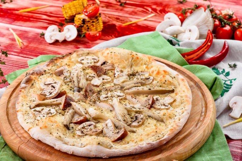 Italiaanse Vegetarische Paddestoelpizza met cheddar op een ronde houten raad op een rode houten achtergrond royalty-vrije stock foto