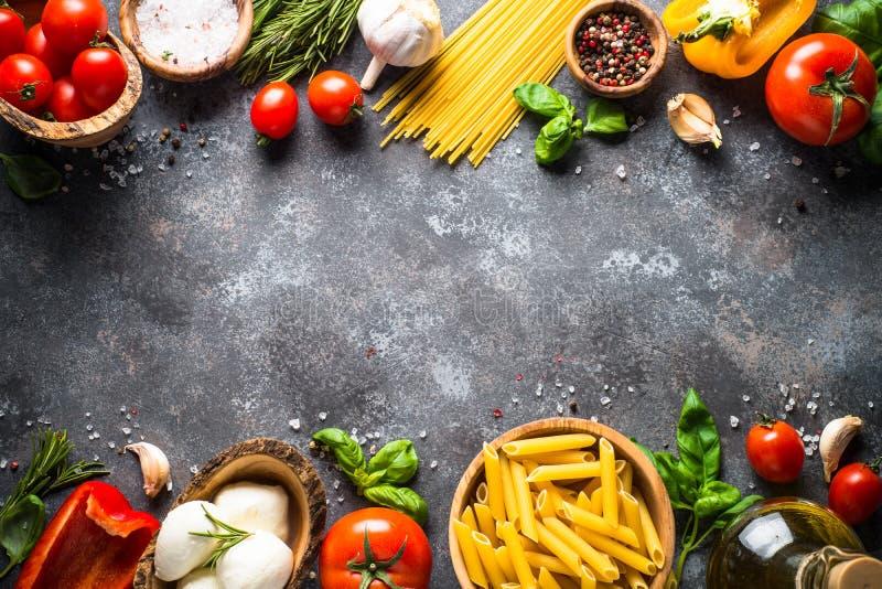 Italiaanse voedselachtergrond Deegwaren, kruiden, groenten op zwarte bovenkant v royalty-vrije stock afbeeldingen
